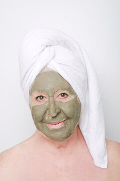 mujer mayor con sobre peso mirando a camara con una mascarilla de arcilla verde y una toalla en la cabeza