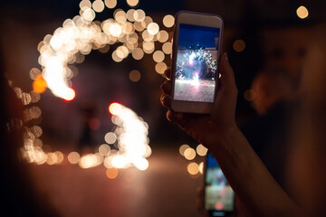 A woman shoots fireworks on a smartphone. The lights are beautifully reflected in her glasses