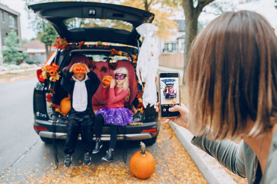 Trick or trunk. Children boy and girl with red pumpkins celebrating October Halloween holiday in trunk of car outdoors. Mother taking pictures of kids on smartphone camera for social media.
