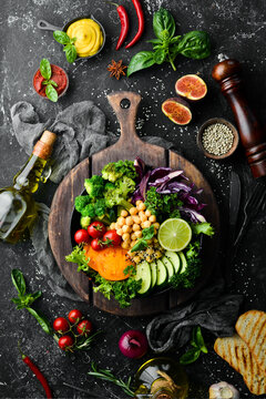 Vegan Buddha bowl: chickpeas, broccoli, tomatoes and cucumber on a black stone plate. Food. Top view. Free space for your text.