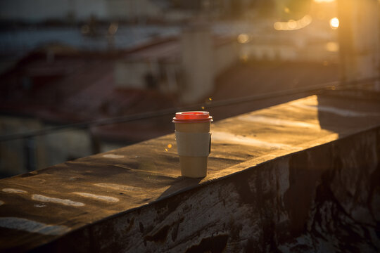A disposable cup of coffee with a red lid stands on the rusty roof of the city at sunset. View of the old town of St. Petersburg from the roof. Guided tours of the rooftops.