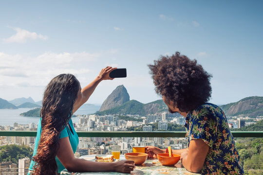 A multi-ethnic couple breakfasting and taking a mobile phone photo of Sugar Loaf and the Rio skyline, Rio de Janeiro, Brazil