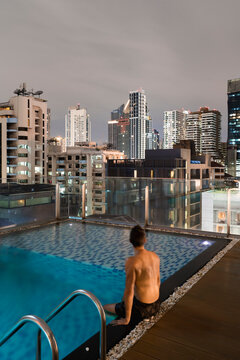 Man relaxing on the rooftop at night. Nice Cityscape