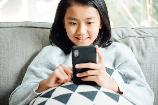 Cute teenager school girl using smart phone