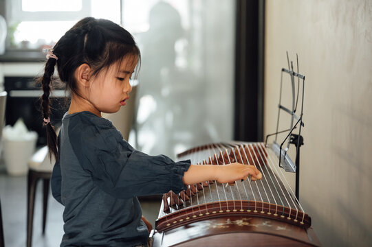 Cute little playing traditional musical instrument zither at home