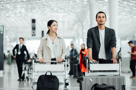 Business people traveling at airport and pushing trolly