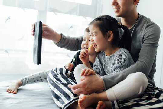 Young father and his kids using tablet together at home