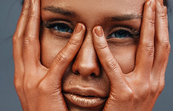 Lady with bronzed skin hiding face