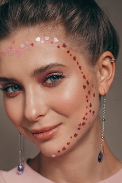 Stylish young woman with hearts on face