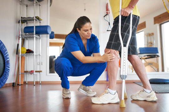 Physiotherapist giving a treatment of a patient with knee problems