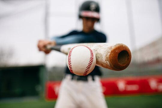 Batter hitting baseball ball with bat