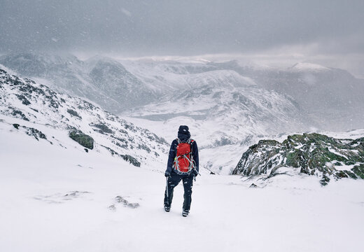 Winter mountaineer using Ice Axe and crampons below Great End. Esk Hause, Cumbria, UK.