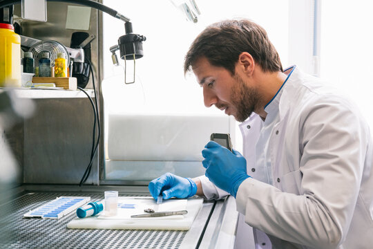 Side view of man in lab coat examining samples and recording results with voice recorder while working in innovative laboratory.