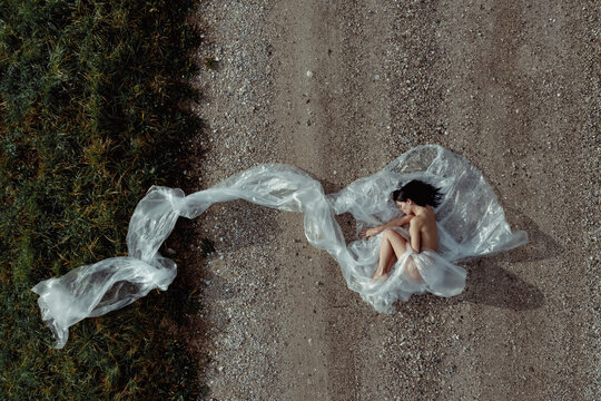 Aerial view of a woman in nature covered with plastic. Plastic concept