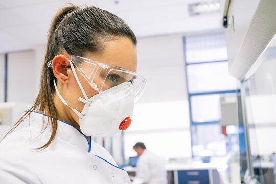 Young woman wearing safety mask and goggles while working in innovative laboratory.