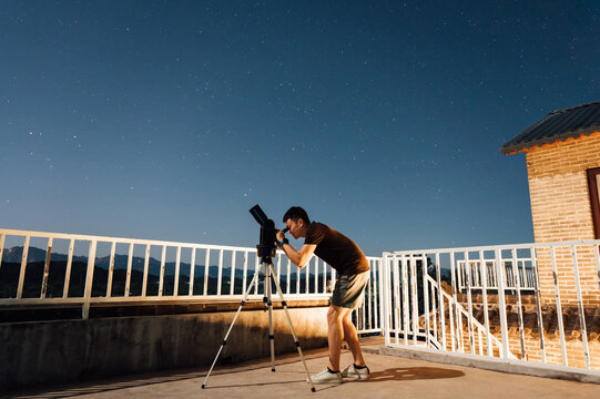 Men looking at stars with telescope