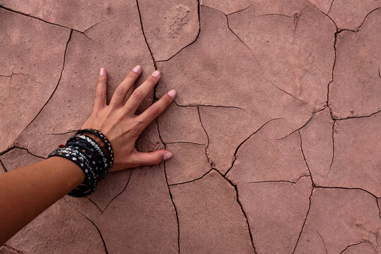 Hand of a woman on The Background Of Cracked Earth