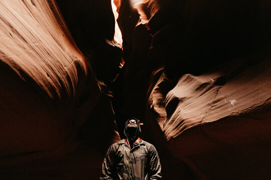 A man looking up at light / sky in Antelope Canyon in Arizona