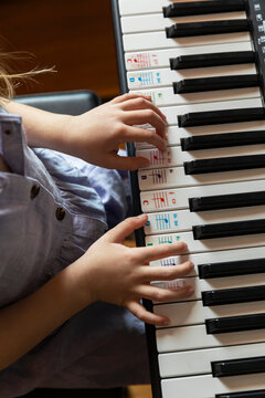young child with hands on keyboard while learning to play piano