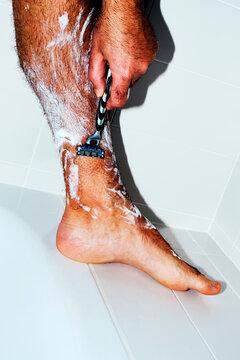man shaving his legs