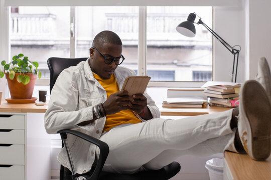 Black man using tablet during break in office