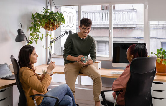 Cheerful man talking with diverse women during break in office
