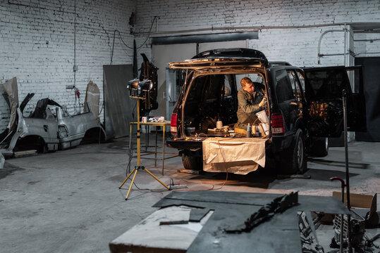 Mechanic repairing car in dark garage