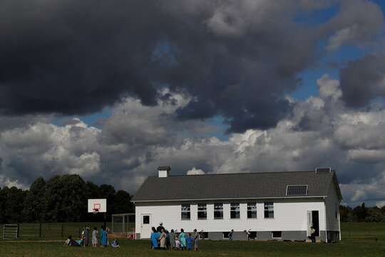 Amish children are seen outside a school building in the countryside of Mesopotamia, Ohio