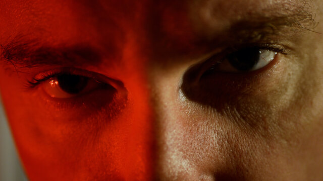 A young man with a serious look. Frowning man in red tones evil smile