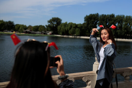 A woman poses for a photo in the tourist area surrounding Houhai Lake during Chinese National Day holidays in Beijing