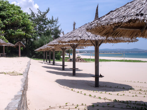 beach area on the seashore near a quarantined hotel. beach umbrellas made of wood and palm leaves. everything around is covered with sand and no traces of a person are visible.