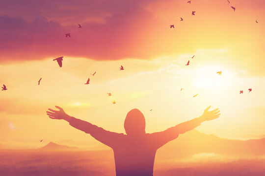 Freedom feel good and travel adventure concept. Copy space of silhouette man rising hands on sunset sky at top of mountain and bird fly abstract background.