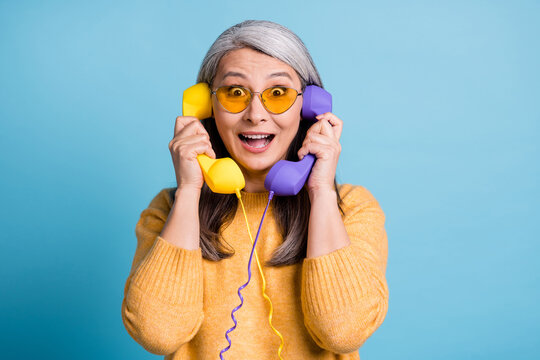 You can't be serious. Photo of charming excited old lady staring shocked look open mouth hold two phones listen new mall discounts sunglass yellow jumper vivid blue color background