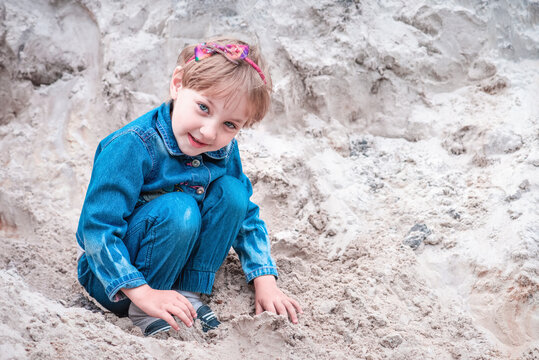 Happy girl in denim suit plays in the sand on the river bank.