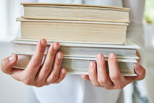 Woman carries stack of books in her arms with hands