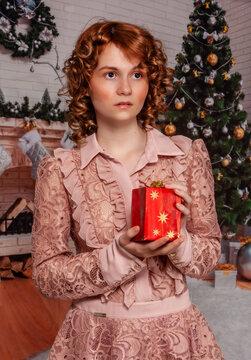 Sehr schöne junge Frau mit roten Haaren in einem Weihnachtlichen Ambiente hält ein Geschenk in der Hand.