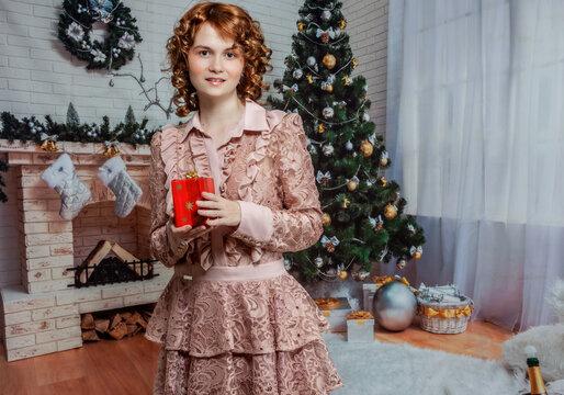 Junge Frau mit roten lockigen Haaren posiert mit einem Geschenk in der Hand vor einem Christbaum