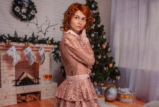 Hübsche junge Frau in einem Raum mit Weihnachtsdekoration. Winterstimmung, gemütliches Zuhause, englischer Stil