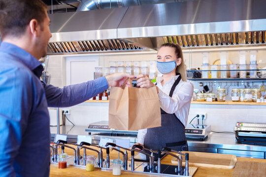 Happy waitress wearing protective face mask serving takeaway food to customer at counter in small family restaurant.