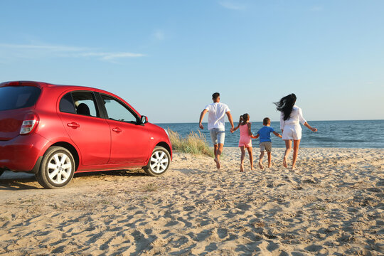 Family running on sandy beach. Summer trip