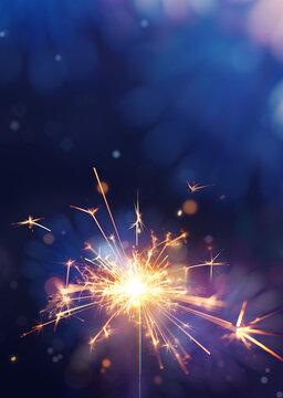 Glittering burning sparkler against fireworks background