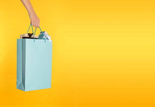 Woman holding paper shopping bag full of gift boxes on yellow background, closeup