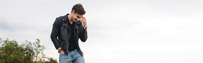 Panoramic shot of man in leather jacket standing outdoors