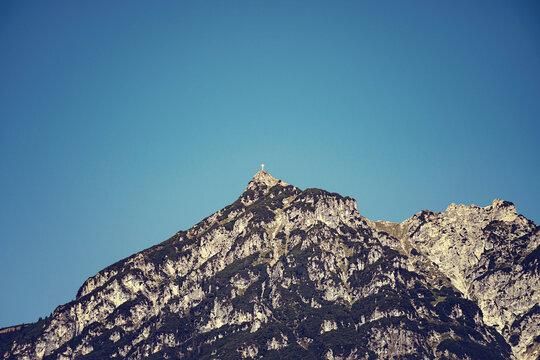 Mountain peaks with summit cross, nostalgic flair.