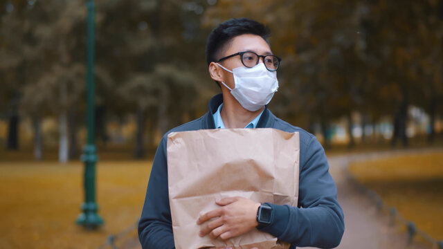 Portrait of asian young man in safety mask walking in autumn park with grocery bag