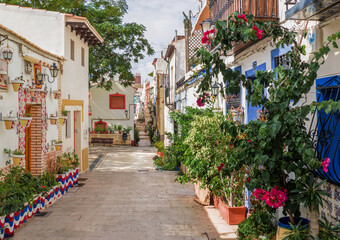 narrow alleys of the picturesque district of santa Cruz with houses adorned with many flower pots.Mediterranean city of Alicante, Spain