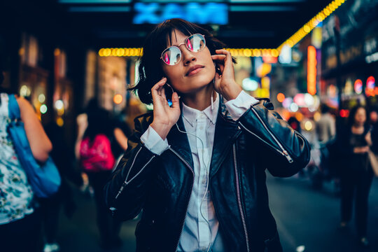 Good looking female millennial in trendy glasses and modern headphones enjoying music podcast, tranquil woman in electronic equipment listening serene audio playlist relaxing at metropolitan street