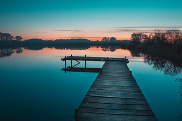 Wooden pier and a view of a calm lake after sunset