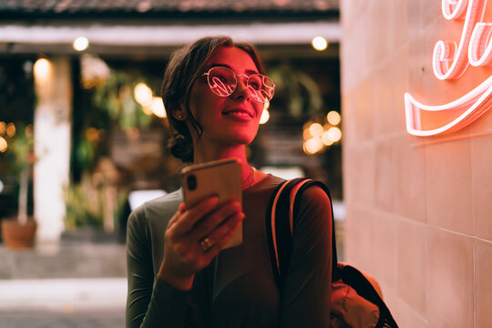 Trendy woman with smartphone on street in neon light