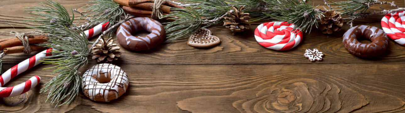 Christmas background with decorations on wooden background.  Christmas ornaments on wood with candy with copy space for your text.
